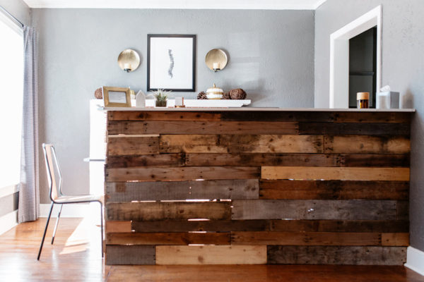 A front desk made of pallet wood is seen in an urgent care waiting room.