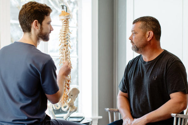 Dr. Shawn Johnston educates a male patient on pain in his spine.