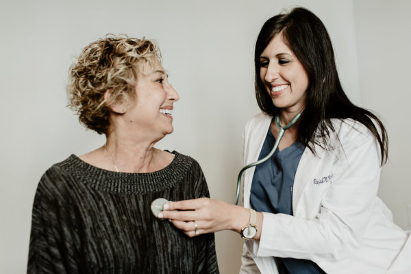 A female nurse practitioner uses a stethoscope on a smiling female patient.