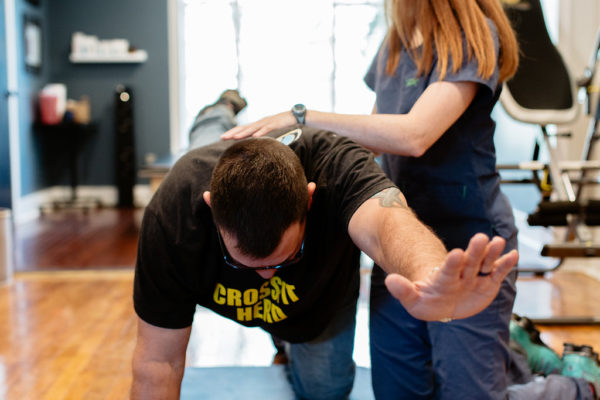 A man performs a stretching exercise while being coached by a female chiropractic assistant.