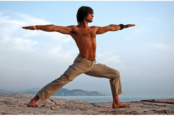 A man uses the warrior pose to stretch his psoas muscle.