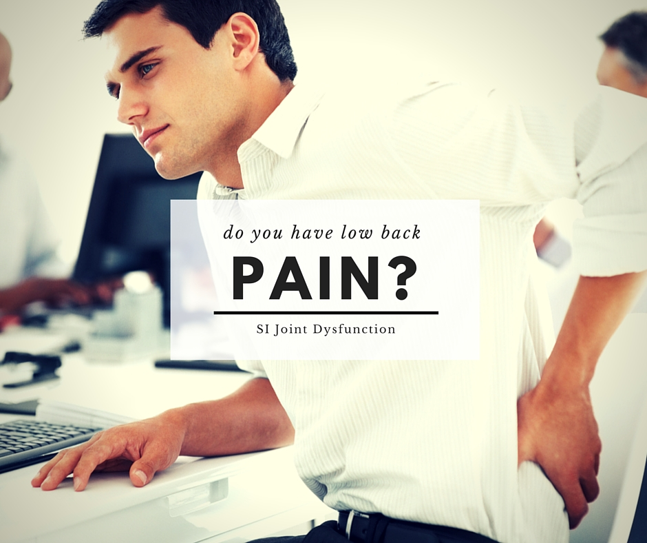 A man holding his back while in lower back pain.